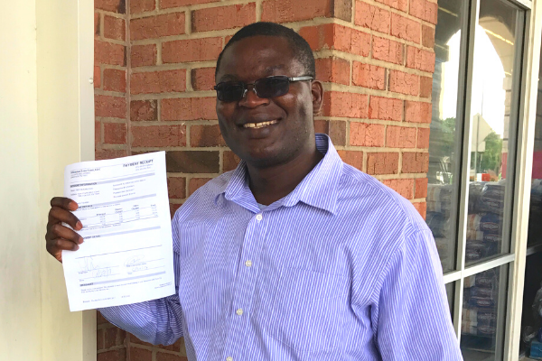 man holding up loan closing document smiling