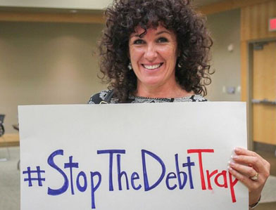 """woman holding sign that says """"Stop the Debt Trap"""""""