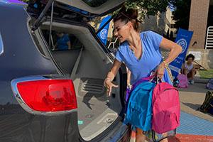woman loading backpacks into car